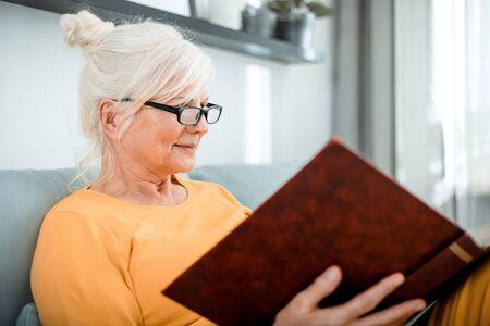 Cheerful senior female holding family photo album sitting on sofa at home Reklamní fotografie - 127359519