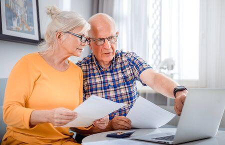 Worried senior couple checking bills using laptop at home