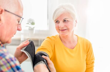 Senior husband doing blood pressure measurement to his wife at home Reklamní fotografie - 127359527