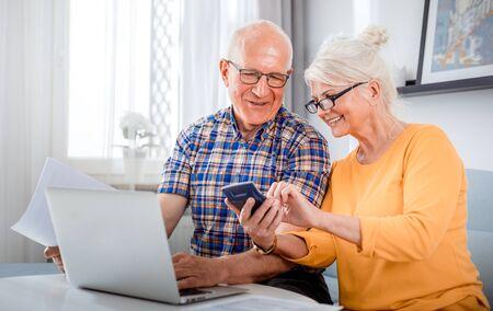 Senior couple checking bills using laptop at home Reklamní fotografie