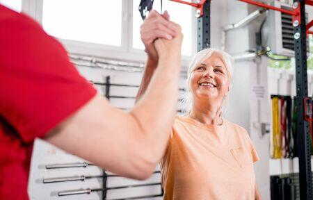 Senior people at the gym giving highfive after training Reklamní fotografie - 127359532