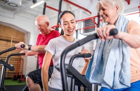 Senior couple biking at the gym with personal trainer Reklamní fotografie - 127359534