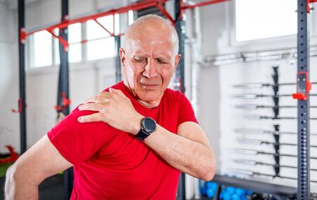 Senior man at the gym suffering from pain in shoulder