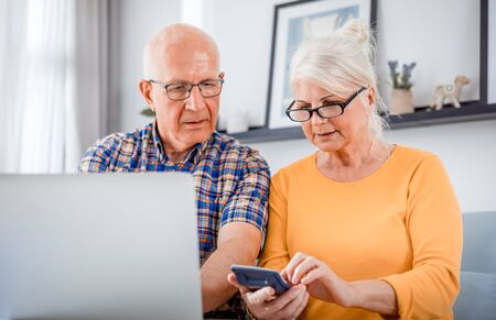 Worried senior couple checking bills using laptop at home Reklamní fotografie - 127359577