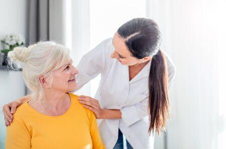 Smiling nurse talking with senior female during home visit Reklamní fotografie - 127359578