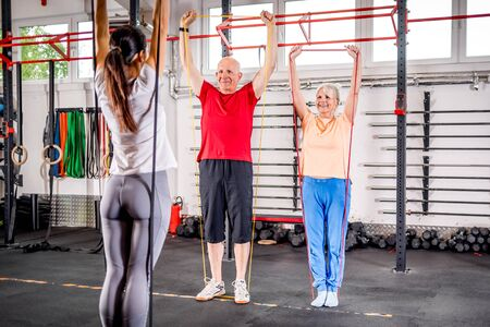 Senior people with trainer using resistance band doing exercises at the gym Reklamní fotografie - 127359677