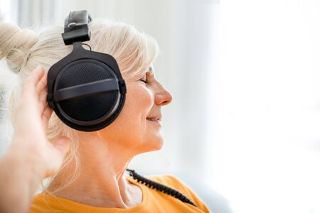 Relaxed senior woman listening her favourite music at home using big headphones 写真素材 - 127359682
