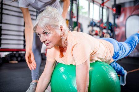 Mujer mayor con entrenador haciendo rehabilitación con pelota de pilates en el centro de rehabilitación