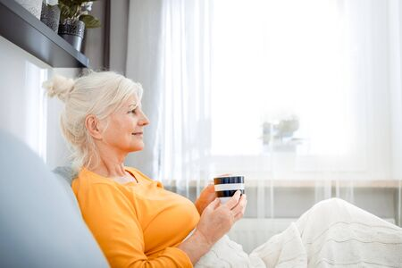 Senior woman at home relaxing on sofa with blanket holding cup of coffee 写真素材 - 127359687