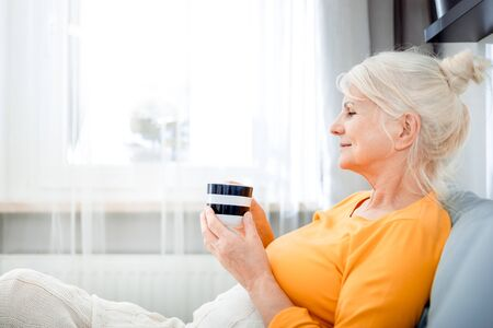 Senior woman at home relaxing on sofa with blanket holding cup of coffee 写真素材 - 127359688