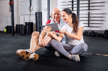 Personal trainer showing results of training on tablet to senior man at the gym Reklamní fotografie - 127359767