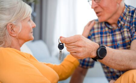 Senior husband giving keys of new house to his wife 写真素材
