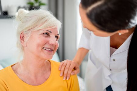 Nurse during home visit talking with senior female and giving treatment advices 写真素材 - 127359781