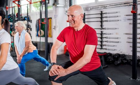 Personal trainer with senior couple doing rehab exercises at the gym 写真素材