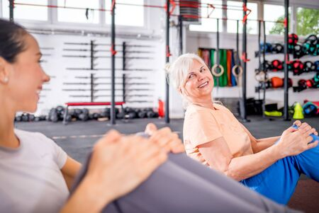 Senior woman workout with trainer at the gym