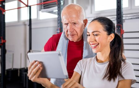 Personal trainer showing results of training on tablet to senior man at the gym 写真素材 - 127359785