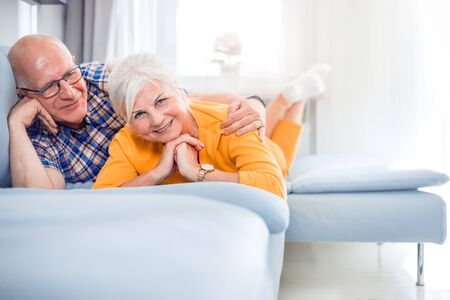 Portrait of cheerful senior couple relaxing and lying on sofa at home 写真素材 - 127359787