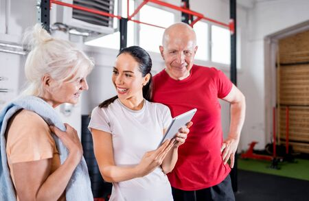 Personal trainer showing results of training on tablet to senior couple 写真素材