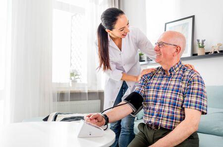 Nurse visiting senior male at home doing blood pressure measurement Reklamní fotografie - 127359799