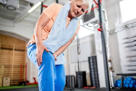 Senior woman at the gym suffering from pain in knee 写真素材 - 127359827