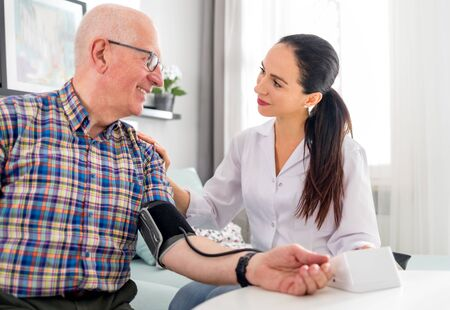 Nurse visiting senior male at home doing blood pressure measurement