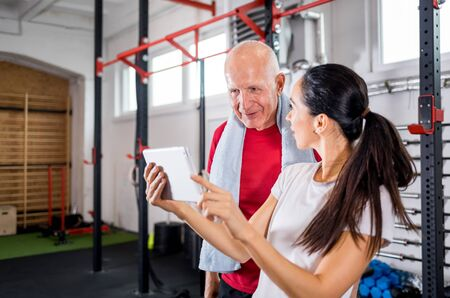 Personal trainer showing results of training on tablet to senior man at the gym 写真素材 - 127359837