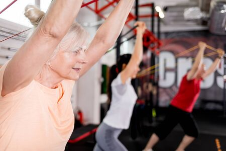 Senior people with trainer using resistance band doing exercises at the gym Reklamní fotografie - 127359841