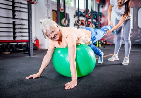 Senior woman with trainer doing rehab using pilates ball in the rehabilitation center Reklamní fotografie - 127359983