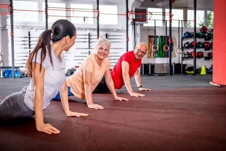 Senior people workout with personal trainer at the gym 写真素材
