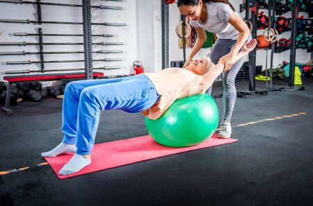 Senior woman with trainer doing rehab using pilates ball in the rehabilitation center 写真素材 - 127359914