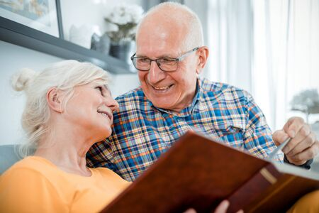 Cheerful senior couple holding family photo album sitting on sofa at home Reklamní fotografie - 127359917