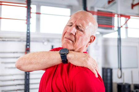 Senior man at the gym suffering from pain in shoulder Reklamní fotografie - 127359922