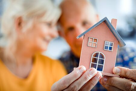 New house concept, happy senior couple holding small home model 写真素材