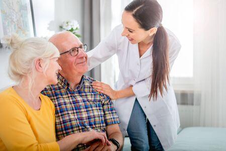 Smiling nurse talking with senior couple during home visit