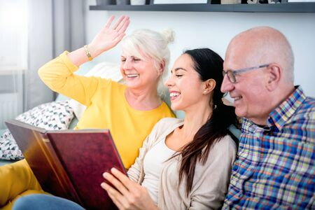Happy senior parents with their daughter looking at photos in family album 写真素材 - 127359989