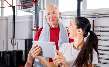 Personal trainer showing results of training on tablet to senior man at the gym 写真素材 - 127359990