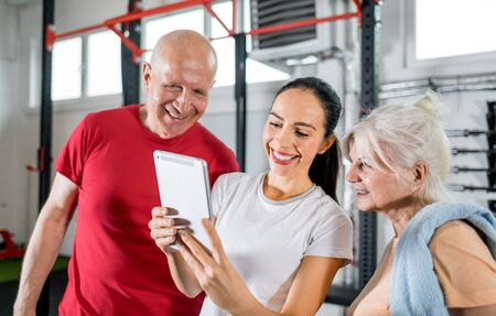 Personal trainer showing results of training on tablet to senior couple 写真素材 - 127359992
