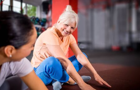 Senior woman workout with trainer at the gym 写真素材 - 127359995