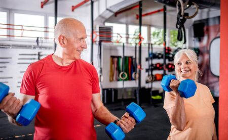 Senior people with dumbbells doing exercises at the gym 写真素材 - 127359997