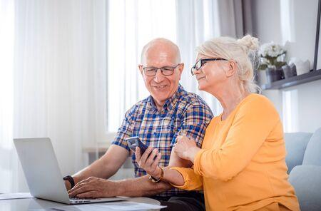 Senior couple checking bills using laptop at home 写真素材