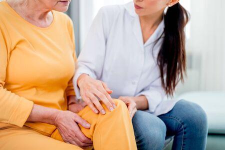 Nurse checking knee pain to senior female during home visit