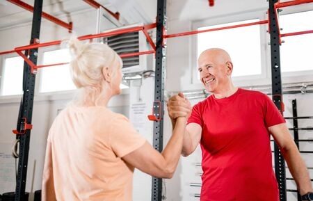Senior people at the gym giving highfive after training 写真素材 - 127360197