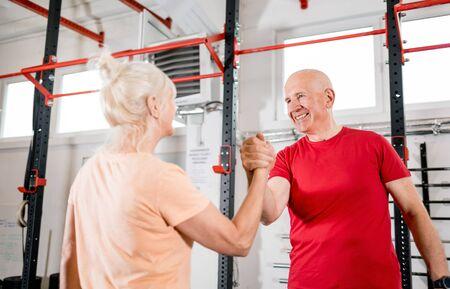 Senior people at the gym giving highfive after training Reklamní fotografie - 127360197