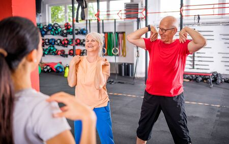 Senior people workout with personal trainer in rehabilitation center Reklamní fotografie - 127360198