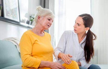 Nurse checking knee pain to senior female during home visit Reklamní fotografie - 127360203