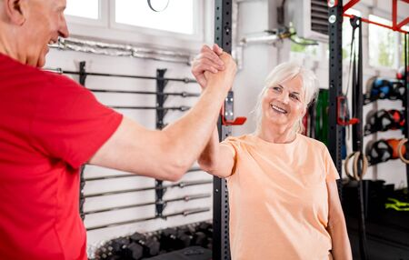 Senior people at the gym giving highfive after training 写真素材 - 127360205