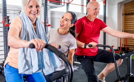 Senior couple biking at the gym with personal trainer Reklamní fotografie - 127360207