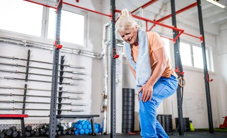 Senior woman at the gym suffering from pain in knee Reklamní fotografie - 127360209