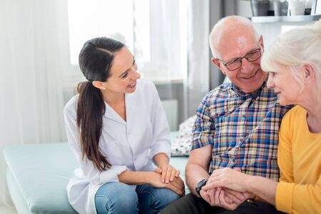 Infirmière souriante parlant avec un couple de personnes âgées lors d'une visite à domicile Banque d'images