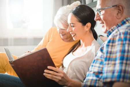 Senior couple with their daughter looking at photos in family album together